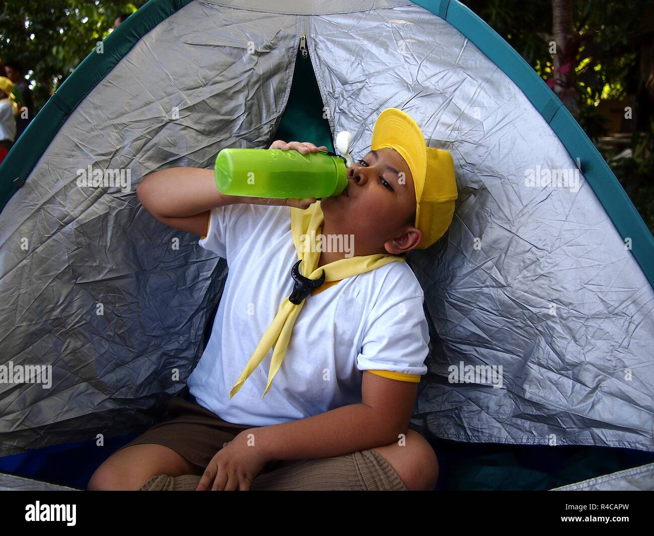 Photo of a young boy scout inside a camping tent drinking water - Stock Image