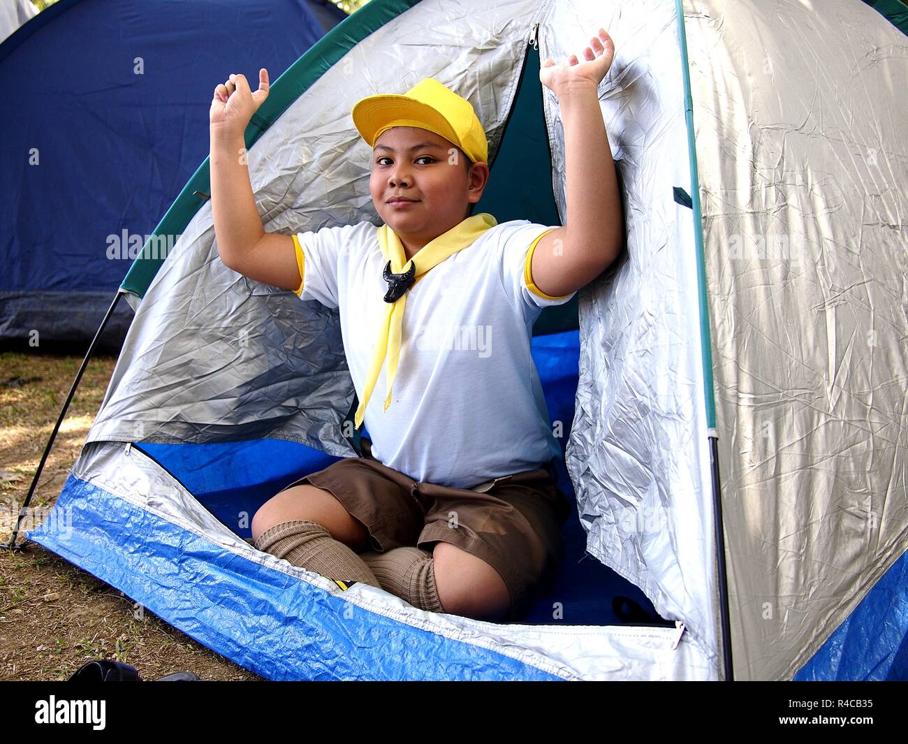 Photo of a young boy scout inside a camping tent - Stock Image