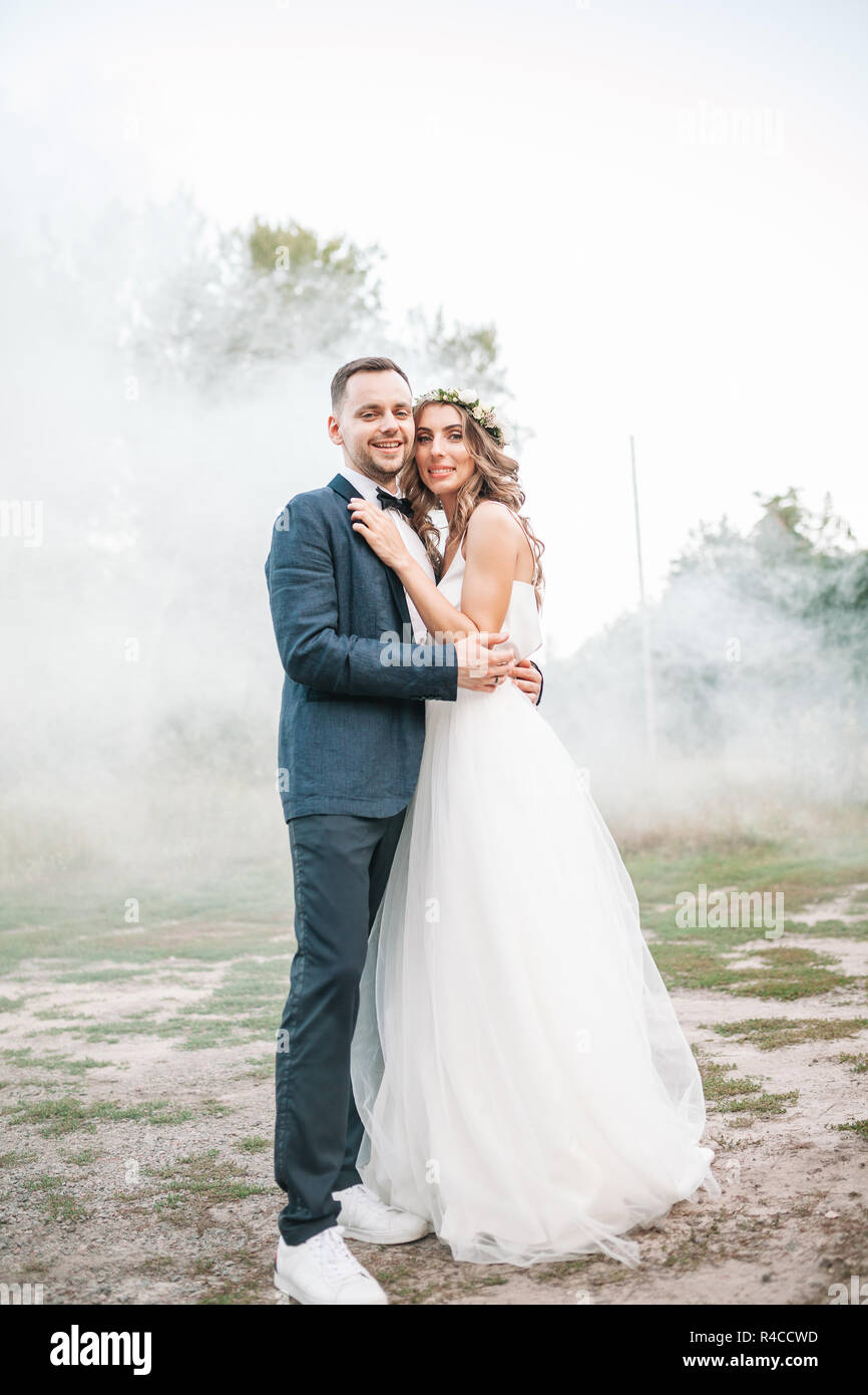 Beautiful bride and groom. Wedding ceremony in nature. Smoke bombs - Stock Image