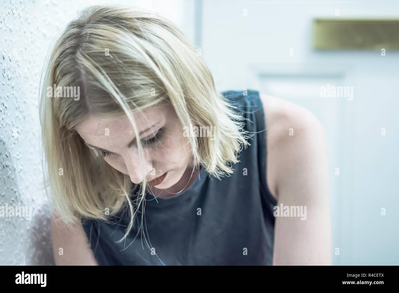 High key soft portrait of young woman looking down expressing sadness or melancholy.Natural lighting and authentic look.Blurred door in background. - Stock Image