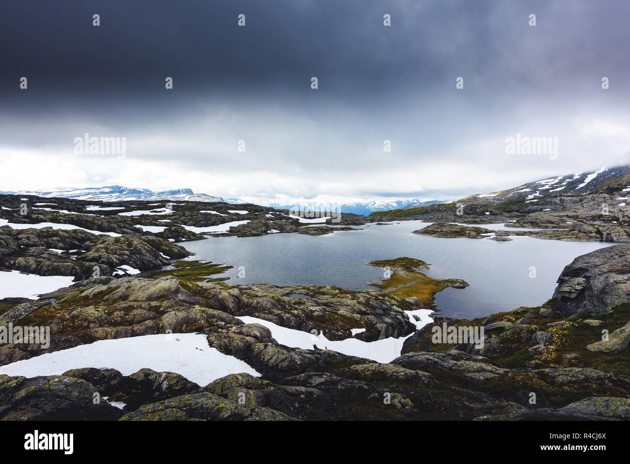 Typical norwegian landscape with snowy mountains and clear lake near the Trolltunga rock - most spectacular and famous scenic cliff in Norway - Stock Image