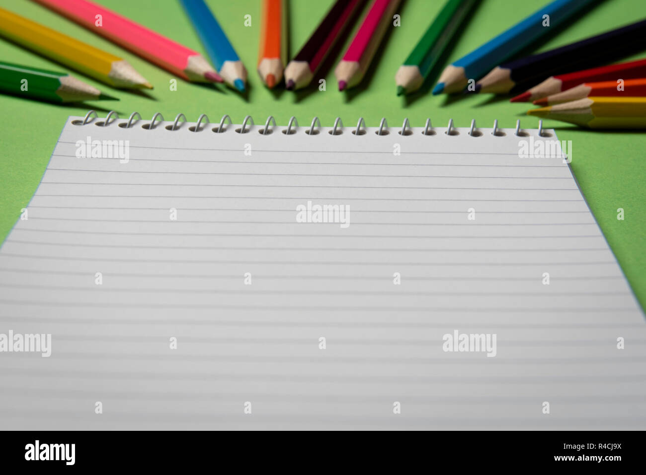 Spiral Notebook Blank Page On A Green Table With Many Colored Wooden