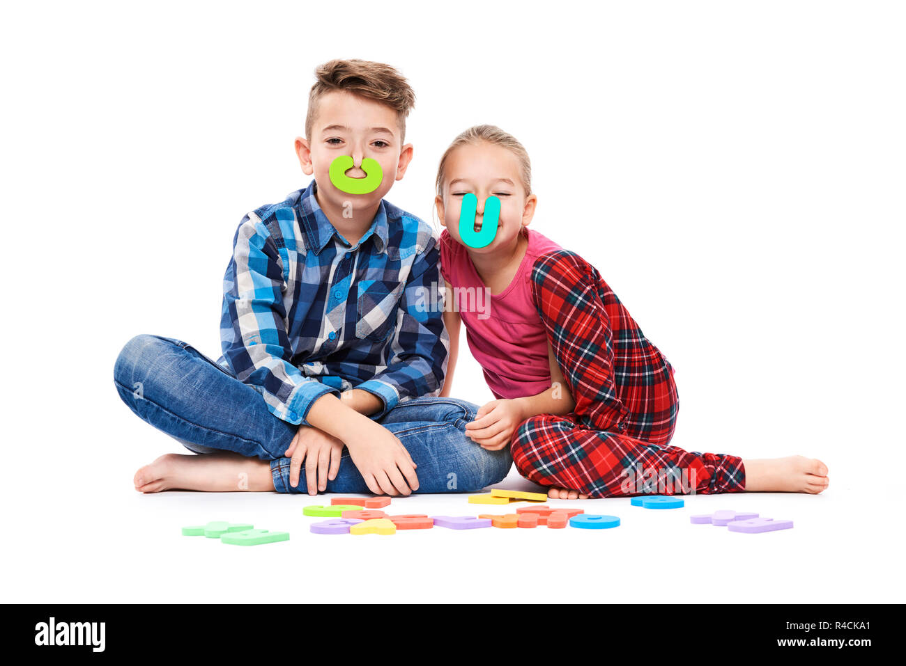 Cute children with large colorful alphabet letters on white background. Kids speech therapy concept. Speech impediment, logopedy background. - Stock Image