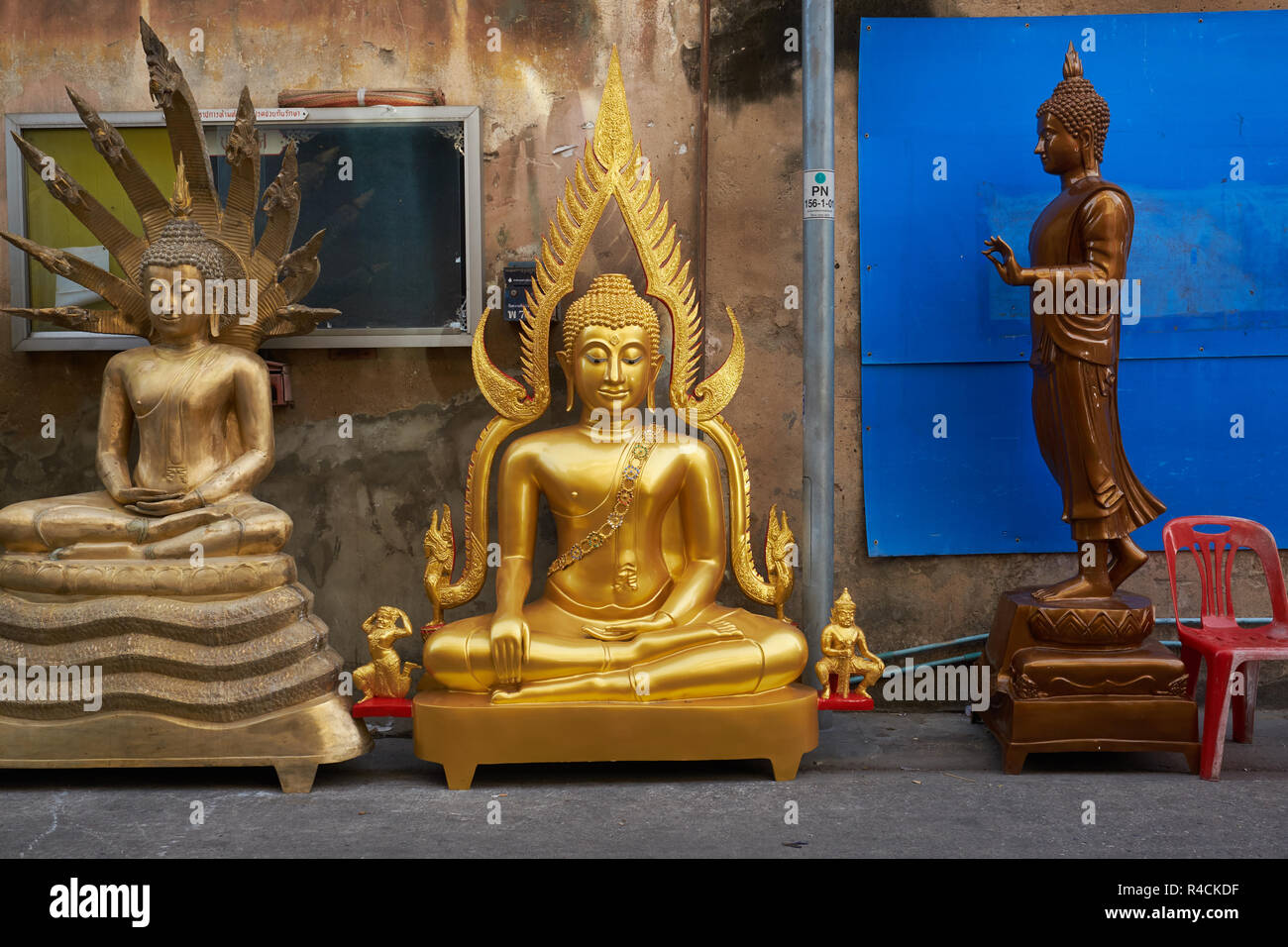 Outside a factory for religious artifacts in Bamrung Muang Rd., Bangkok, Thailand, Buddha statues await transportation to their buyers - Stock Image