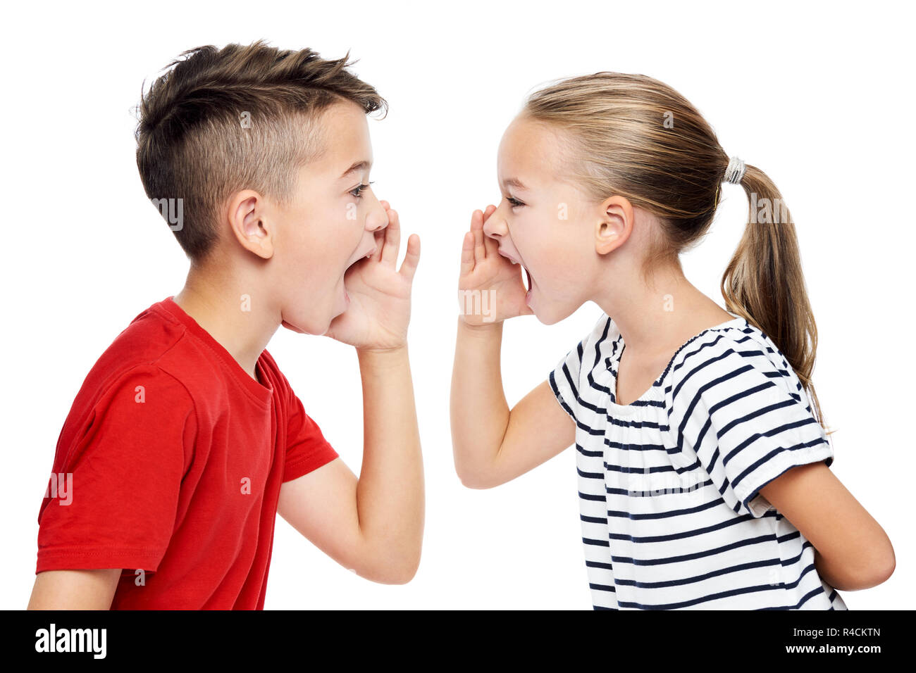 Young children facing eachother and shouting. Speech therapy concept over white background. - Stock Image