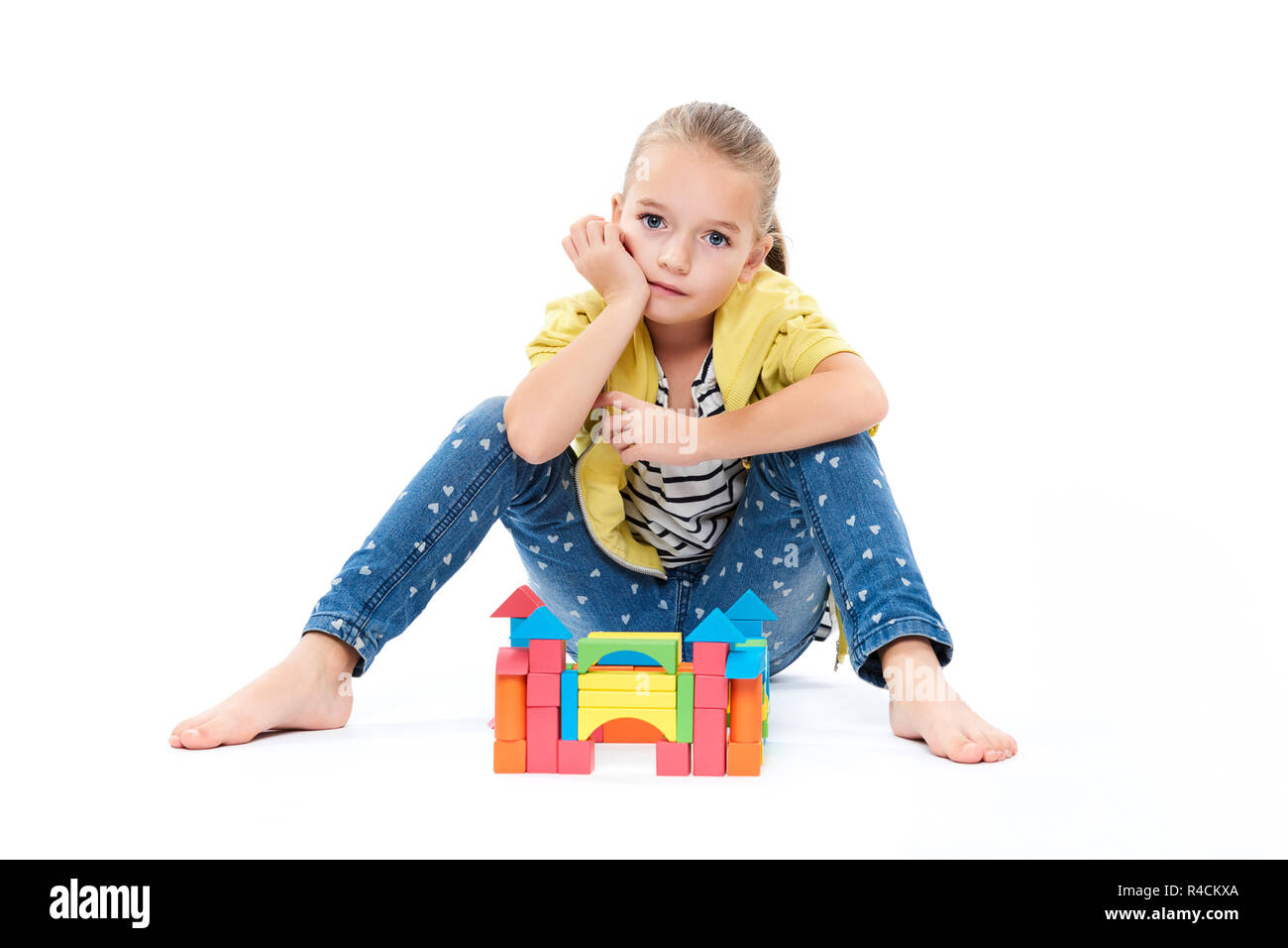 Young girl at behavior therapy, building a castle with wooden toy block. Child play therapy concept on white background. - Stock Image