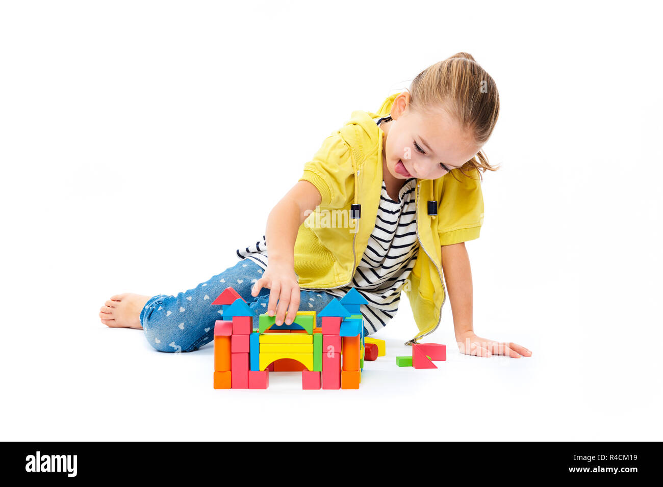 Young girl building a castle with wooden toy block. Child play therapy concept on white background. - Stock Image