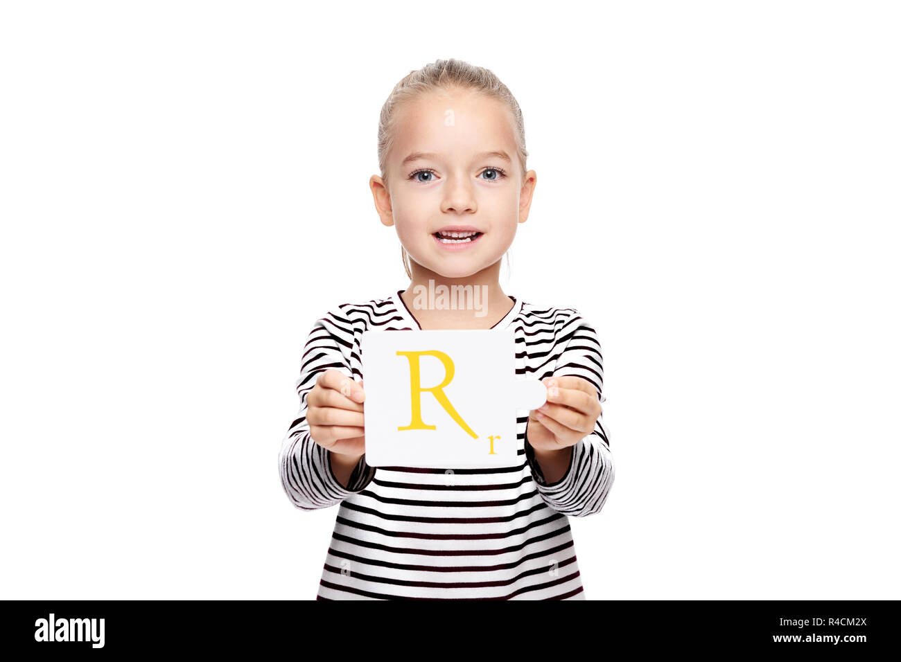 Young girl holding a card with letter R. Speech therapy concept on white background. Correct pronounciation and articulation at preschool age. - Stock Image