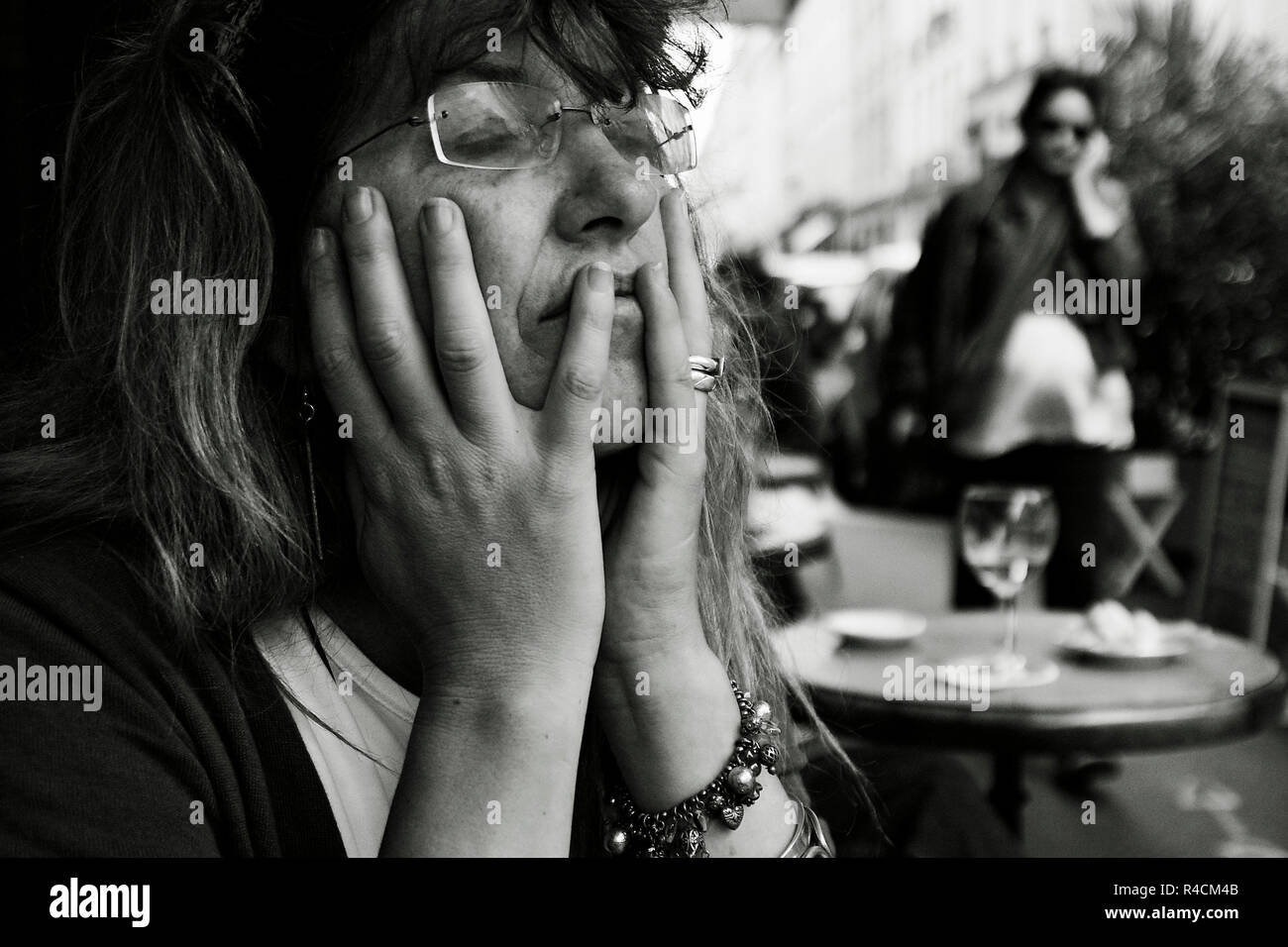 woman, eyes shut, head in hands dreaming, sitting at outside cafe table, - Stock Image
