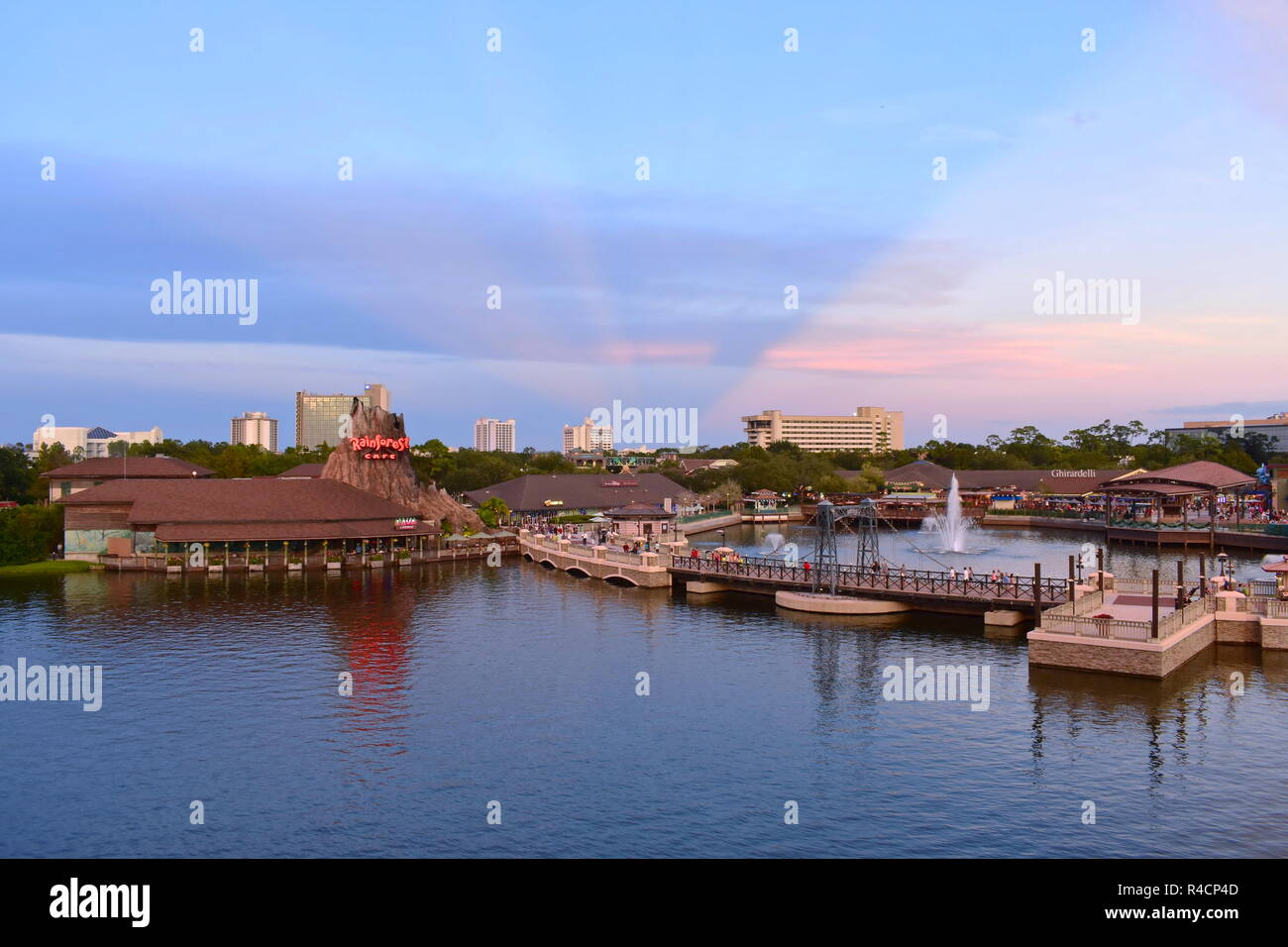 Orlando, Florida. November 18, 2018 Panoramic view of Volcano, vintage bridge , hotels and outside market on sunset with magenta rays at Disney Spring - Stock Image