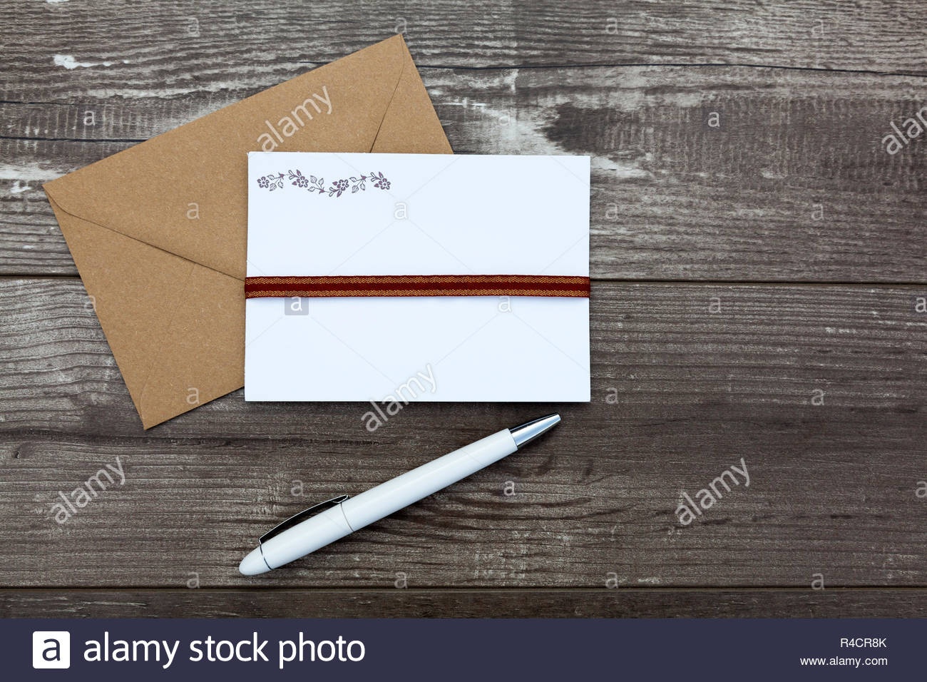 Letter writing concept - Pen, writing paper and envelope on a wooden background - Stock Image