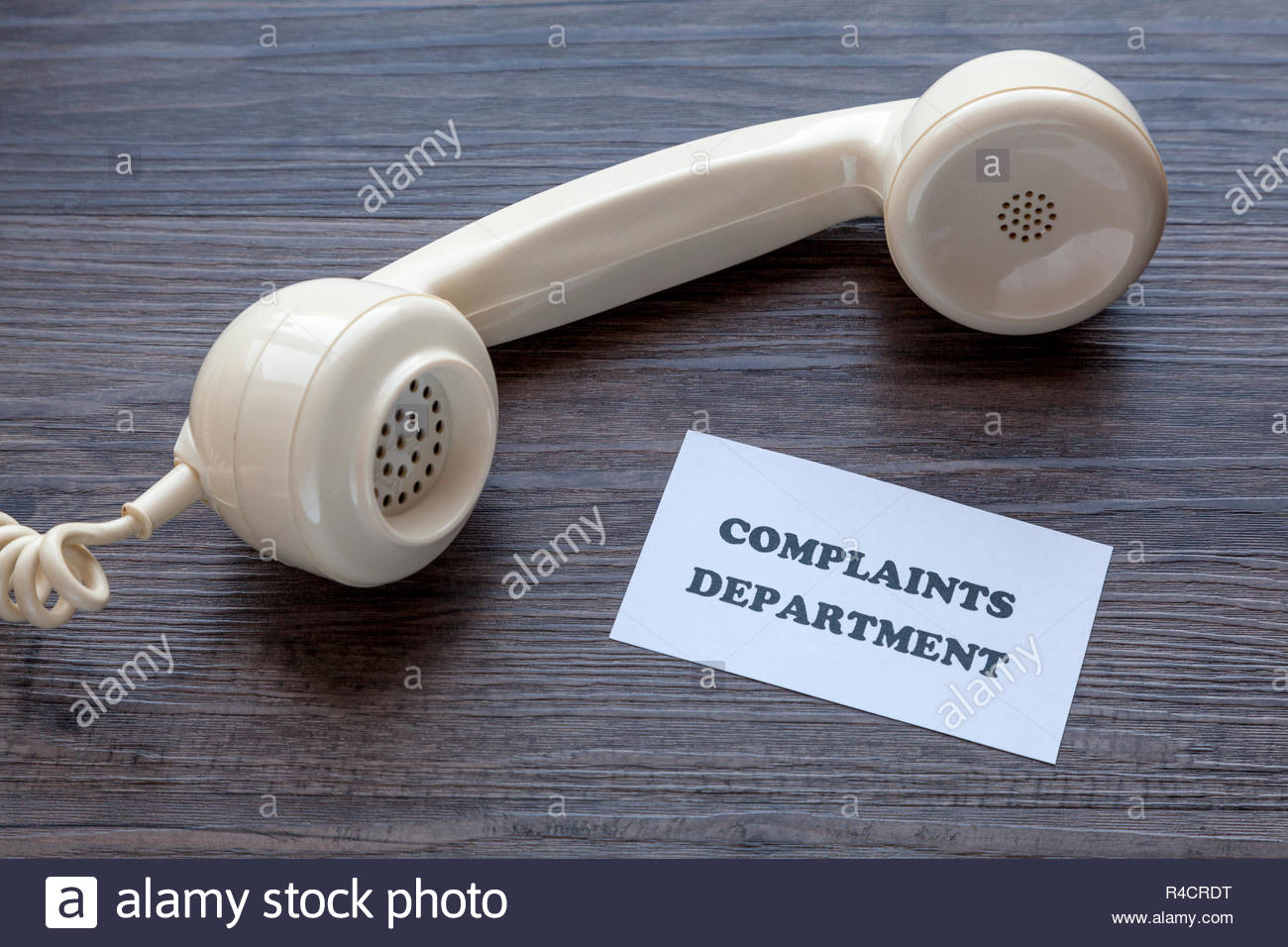 Classic telephone receiver with note - Complaints Department - Stock Image