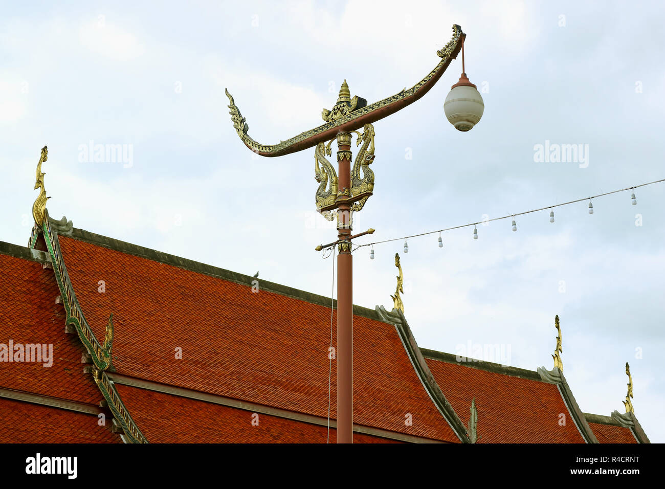 Thai Vintage Racing Boat Shaped Street Lamp against Temple's Tiled Roof and Cloudy Sky, Historic Place in Nan Province, Thailand - Stock Image