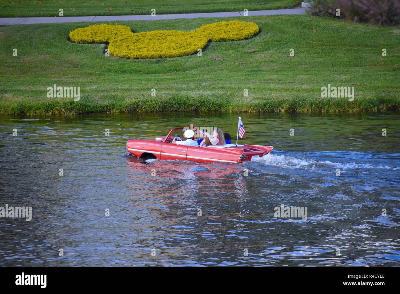 Orlando, Florida.  November 06, 2018 Nice family enjoying Amphibious red car ride over the blue lake  at Lake Buena Vista area Stock Photo