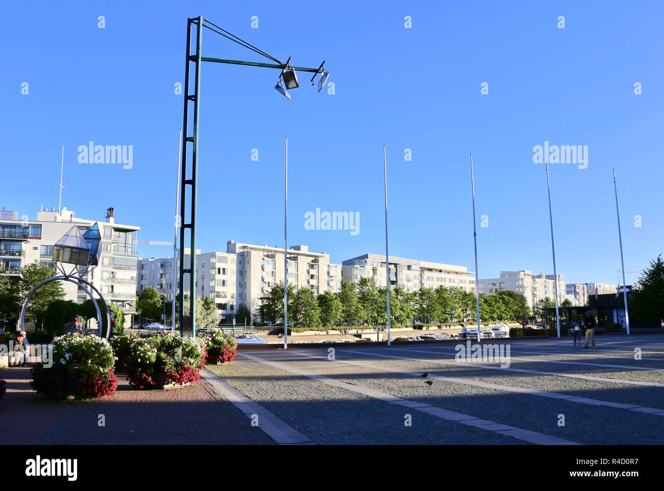 Ruoholahti (Helsinki, the capital of Finland) plaza on summer: residential area next to canal from Bay of Finland, flowers and flagpoles - Stock Image