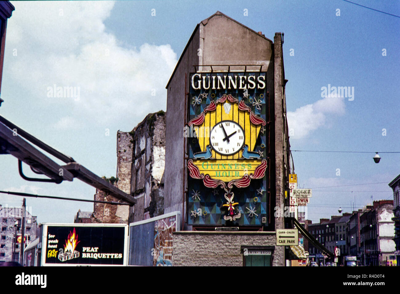 Guinness advertisement and clock on the side of Irwin Brothers watch and jewellery shop which opened in 1897 at 22 Patrick Street, (R445), Limerick, County Limerick, Ireland. The area has been regenerated since this original image taken within the 1960s but after looking on Google maps the shop now looks closed. - Stock Image