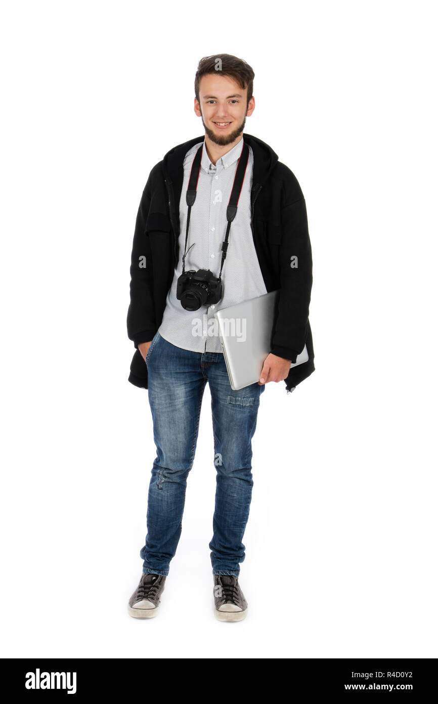 Nerd boy with camera around his neck and computer under his arm, he is standing in the studio and is wearing casual clothes - Stock Image