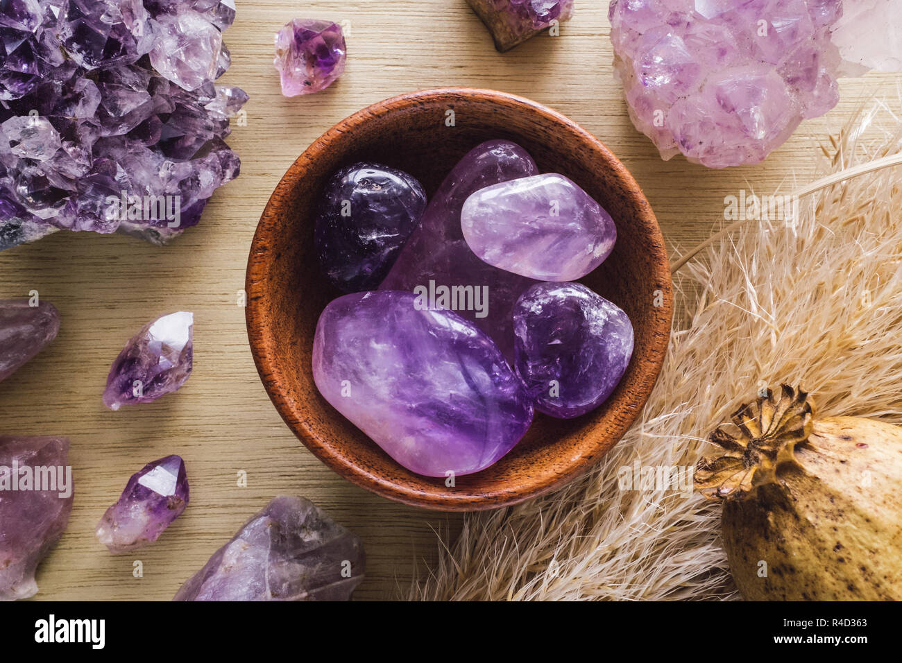 Teak Bowl of Amethyst with Amethyst Crystals and Dried Poppy Flower on Wood Table - Stock Image