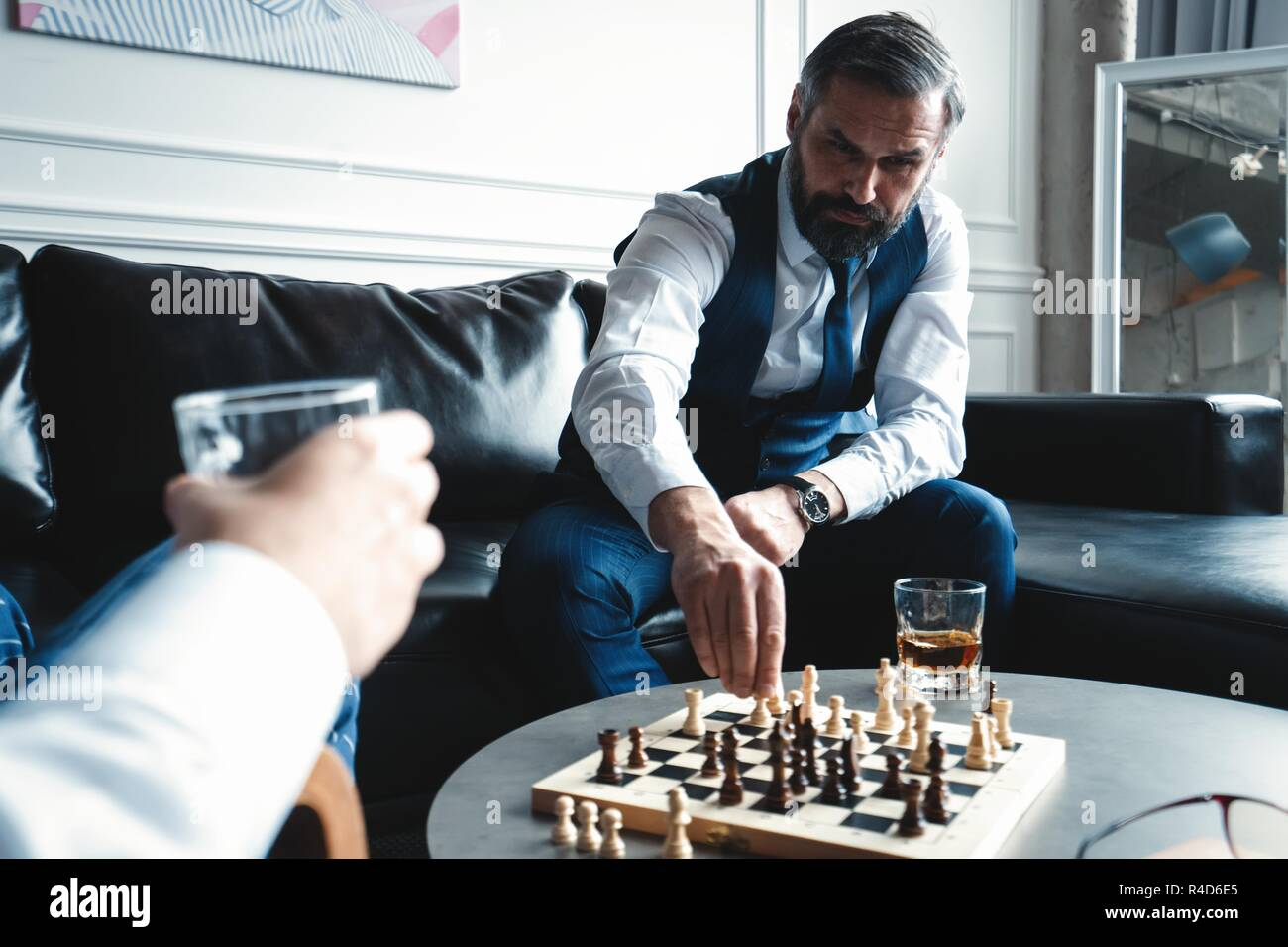 Your move! Two young handsome men in full suits playing chess and smiling while sitting indoors - Stock Image