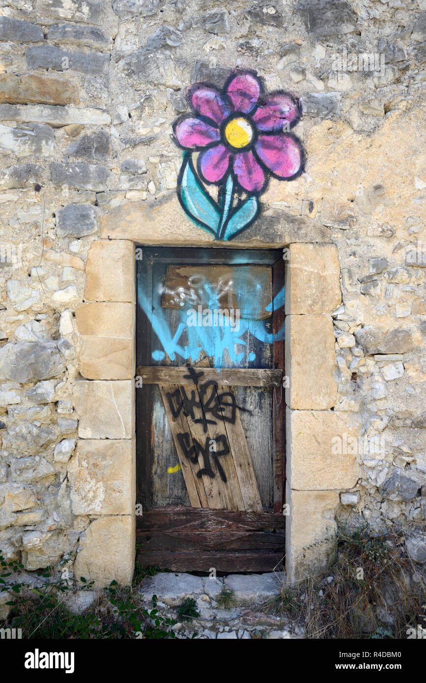 Surreal Graffiti Door & Stylised Flower Painted on Ruined House in the Abandoned Village of Le Vieux-Noyers Noyers Provence France - Stock Image