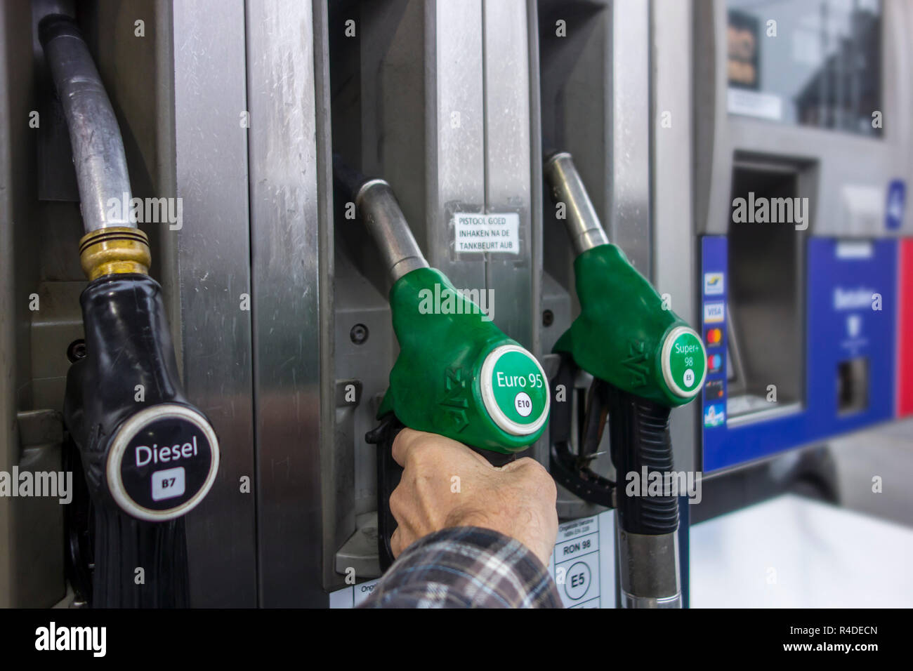 Man selecting petrol fuel pump nozzle at gas station for refueling his car in Europe Stock Photo