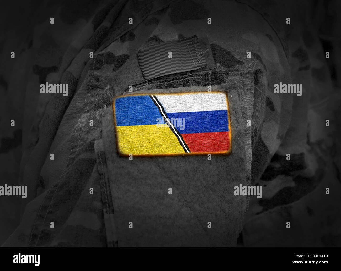 Ukraine vs Russia. Ukrainian Russian conflict. Flag of Ukraine and Russia at military uniform (collage) - Stock Image