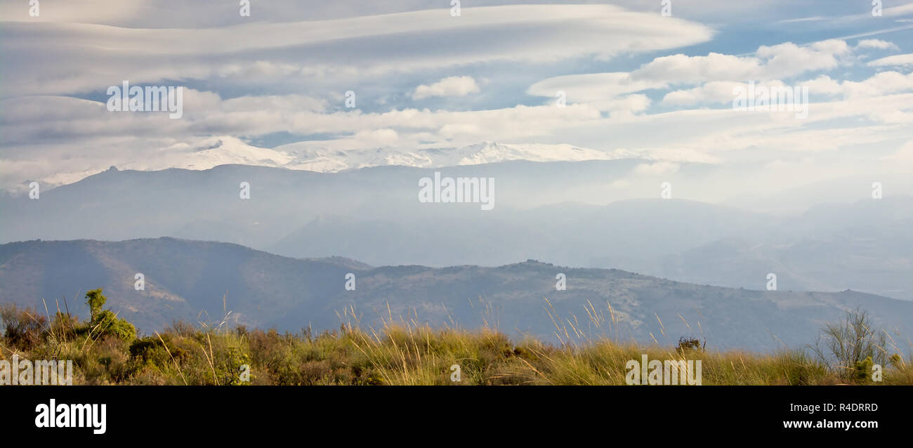 Layers of mountains in Sierra Nevada , the highest ones capped with snow on a sunny day with soft clouds. Andalusia, Spain - Stock Image