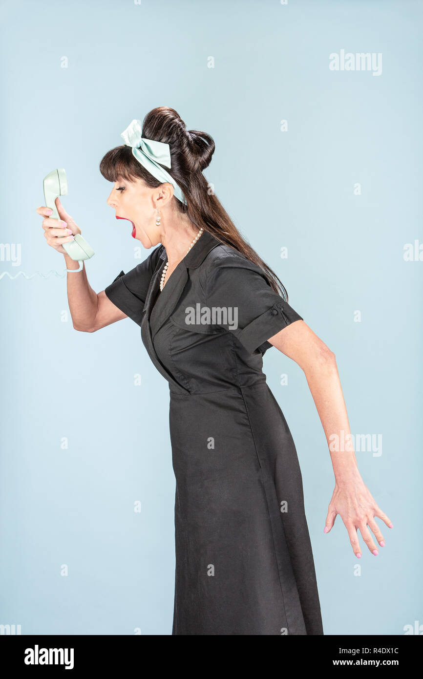 Yelling Retro Woman in Black Dress with Phone Receiver - Stock Image
