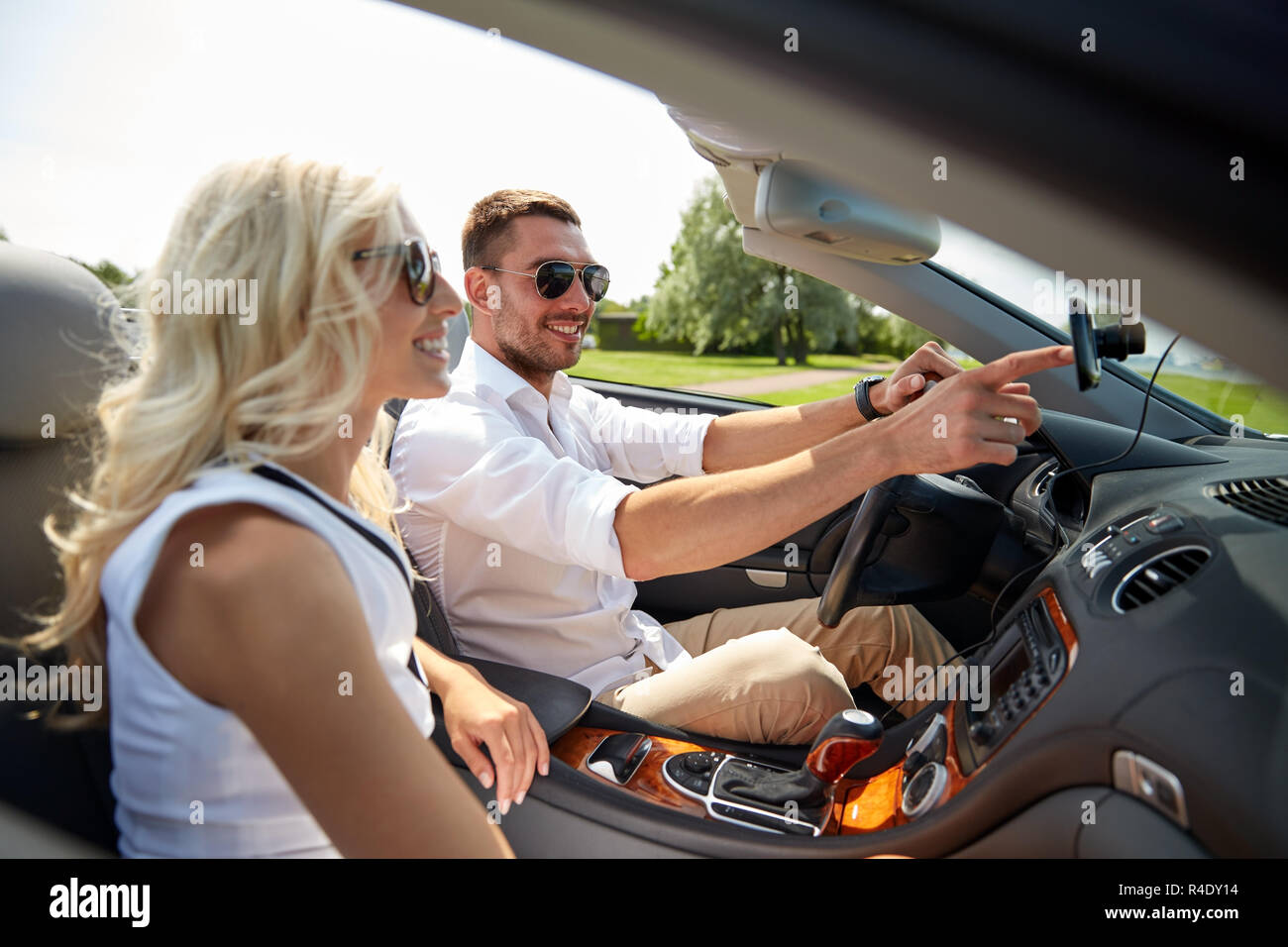 happy couple using gps navigation system in car - Stock Image
