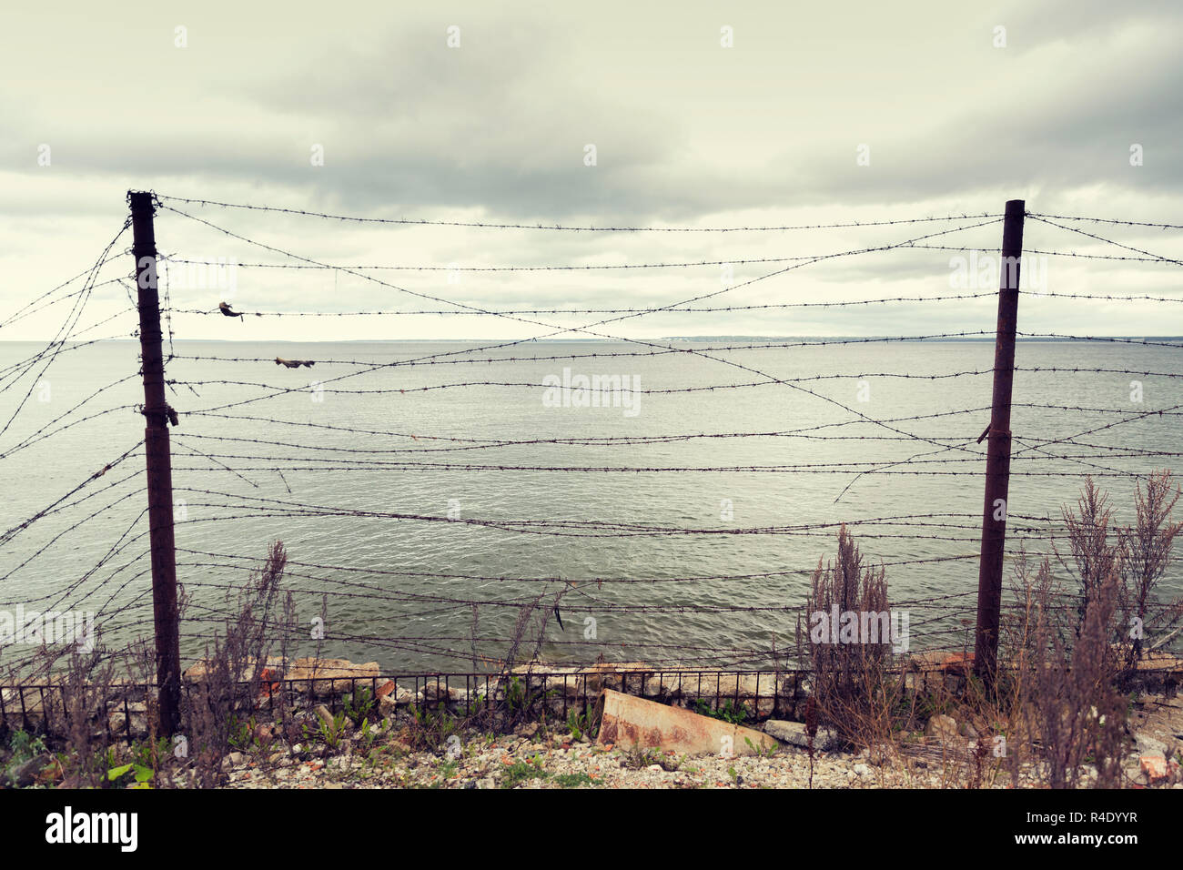 barb wire fence over gray sky and sea Stock Photo