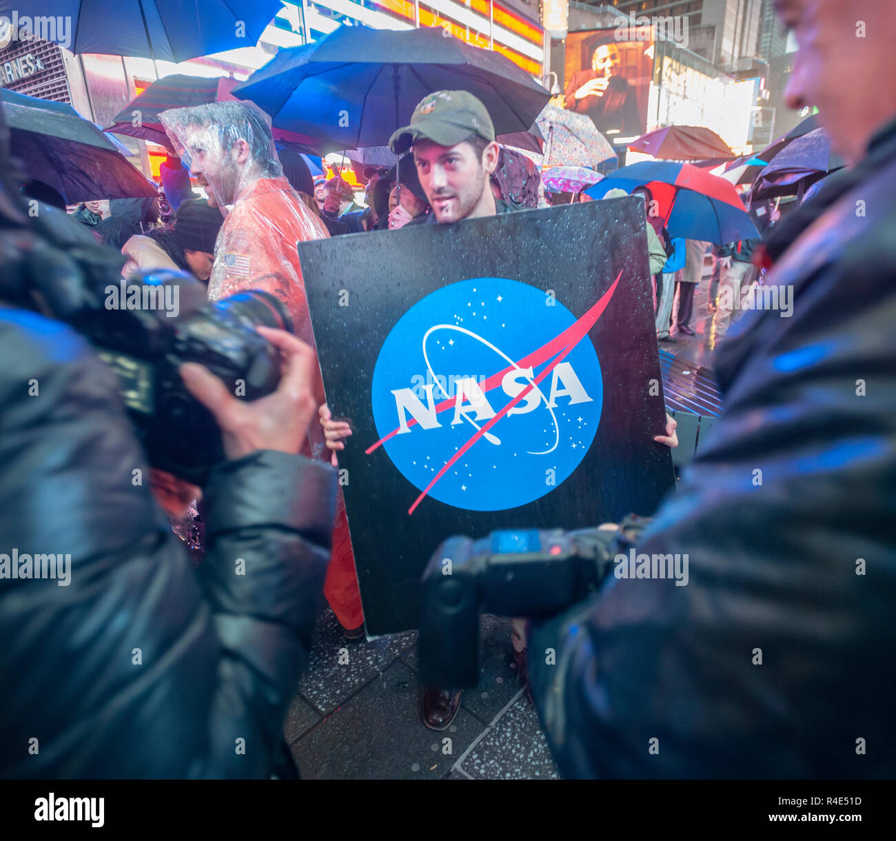 New York, USA. 26th November, 2018. Space exploration enthusiasts brave pouring rain in Times Square in New York to watch Nasa's live coverage of the landing of the Mars InSight lander on Monday, November 26, 2018. The InSight lander survived Nasa's self-proclaimed 'seven minutes of terror' where the probe decelerated from 12,300 mph to 5 mph in the space of seven minutes for the Mars landing. During that time the craft had to rely on its pre-programmed instructions since it could not be steered by Nasa. (© Richard B. Levine) Credit: Richard Levine/Alamy Live News - Stock Image