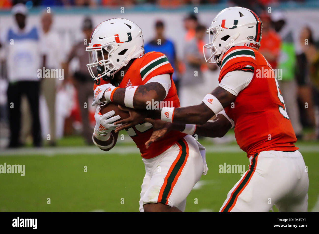 Miami Gardens, Florida, USA. 24th Nov, 2018. Miami Hurricanes running back Cam'Ron Davis (23) runs with the ball after a handoff from Miami Hurricanes quarterback N'Kosi Perry (5) during the college football game between the Pittsburgh Panthers and the Miami Hurricanes at the Hard Rock Stadium in Miami Gardens, Florida. The Hurricanes won 24-3. Mario Houben/CSM/Alamy Live News - Stock Image