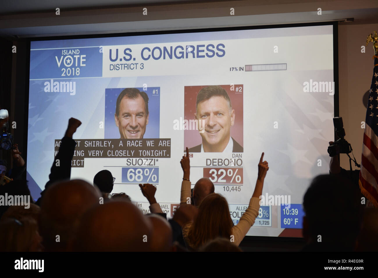 November 6, 2018 - Garden City, New York, United States - Nassau County Democrats watch Election Day results on large screen monitor at Garden City Hotel, Long Island. People lift their arms and cheer as results that U.S. Congressman Tom Suozzi is projected to win over opponent Dan DeBono. Close caption info is about closely watched Congressional race between Liuba Grechen Shirley & incumbent. (Credit Image: © Ann Parry/ZUMA Wire) Stock Photo