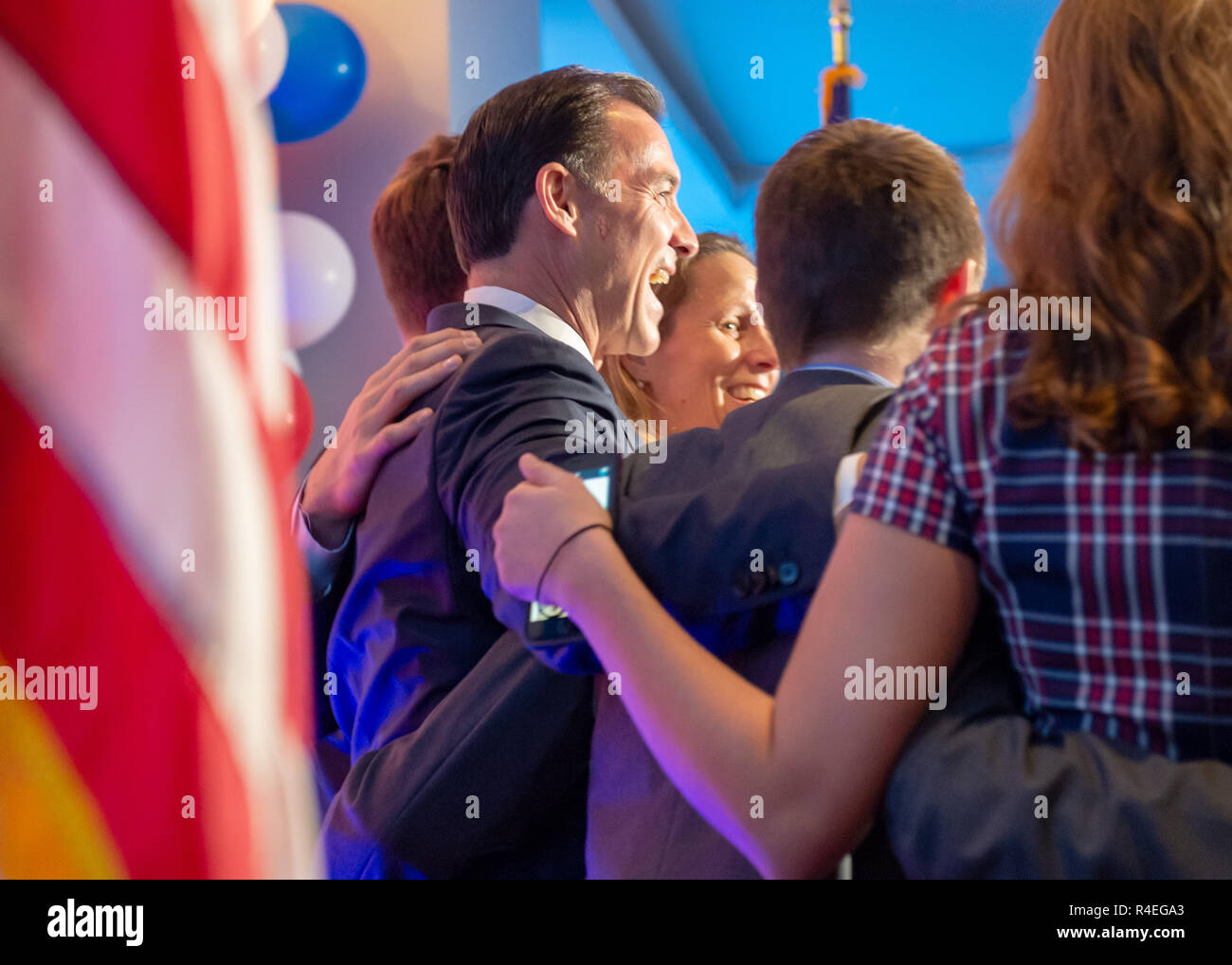 November 6, 2018 - Garden City, New York, United States - At left, Congressman TOM SUOZZI, on stage with his wife HELENE and their daughter and two sons, spoke after winning re-election as U.S. Representative for New York's 3rd district. Nassau County Democrats watched Election Day results at Garden City Hotel, Long Island. (Credit Image: © Ann Parry/ZUMA Wire) Stock Photo