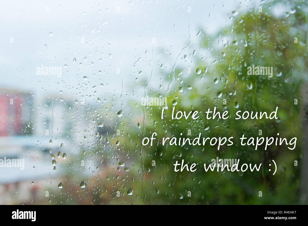 Rain drops on window with text - 'I love the sound of raindrops tapping the windows' - Stock Image