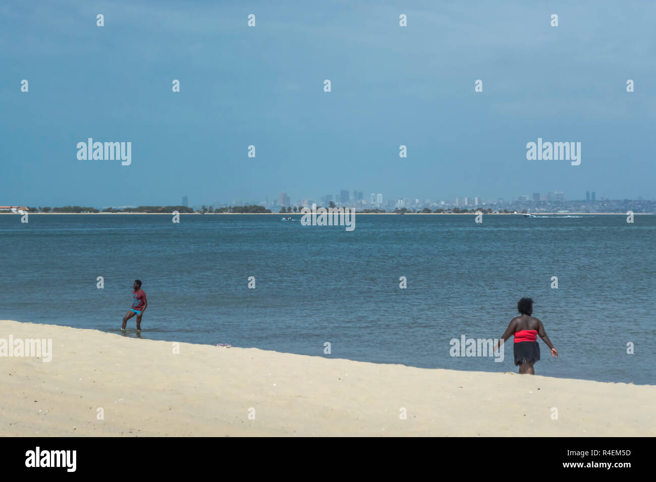 Luanda/Angola - 11 11 2018: View at the beach on Mussulo Island, with a woman walking and a man inside the water ocean, jet boats on water, Luanda cit - Stock Image