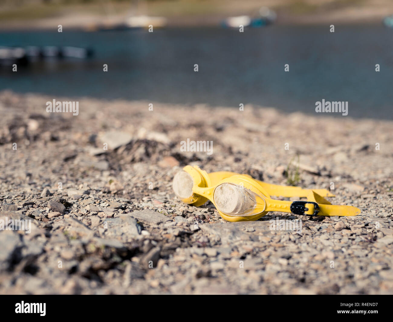 Old, dirty yellow swimming goggles lying on a beach - Stock Image