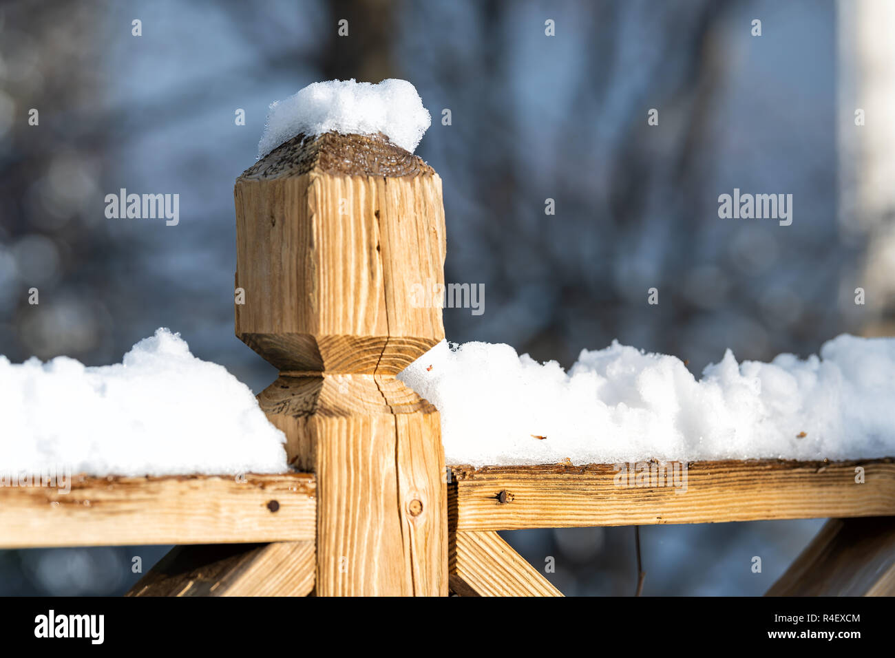 Closeup of wooden deck fence railing, pole, post covered, in piled, pile of snow after heavy snowing snowstorm, storm at house, home, residential neig - Stock Image