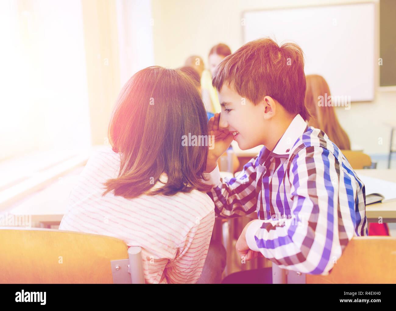 smiling schoolgirl whispering to classmate ear - Stock Image
