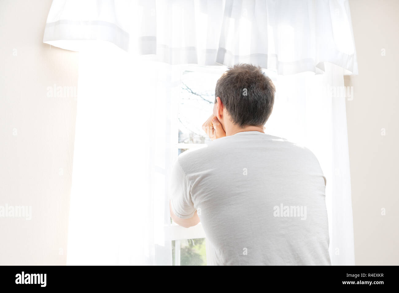 Back of one young male, man, standing, leaning arms, hands against head, looking out, through in white, bright room of house, home, apartment, sunny l - Stock Image