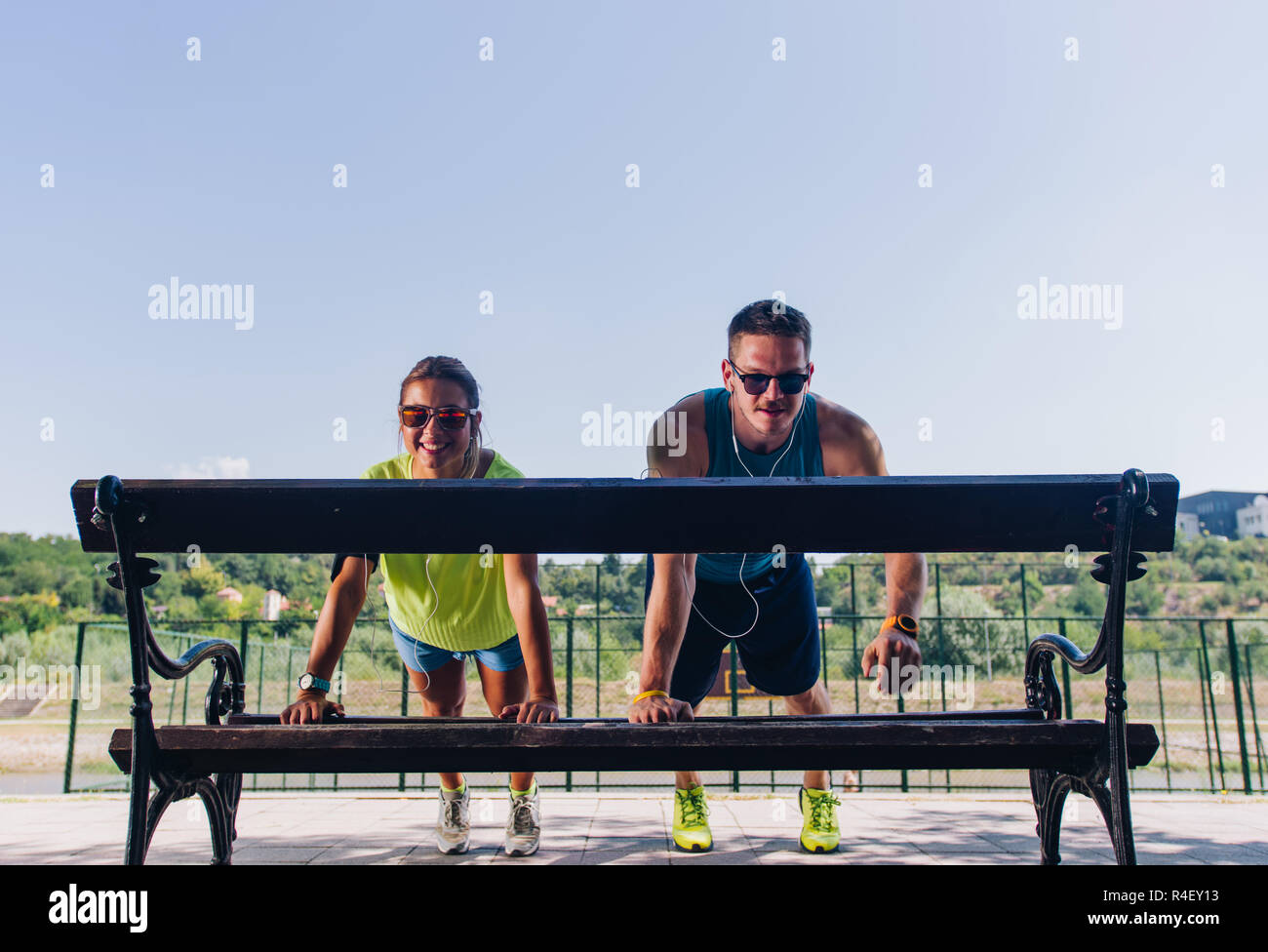 Two runners stretching and warming up in park before training - Stock Image