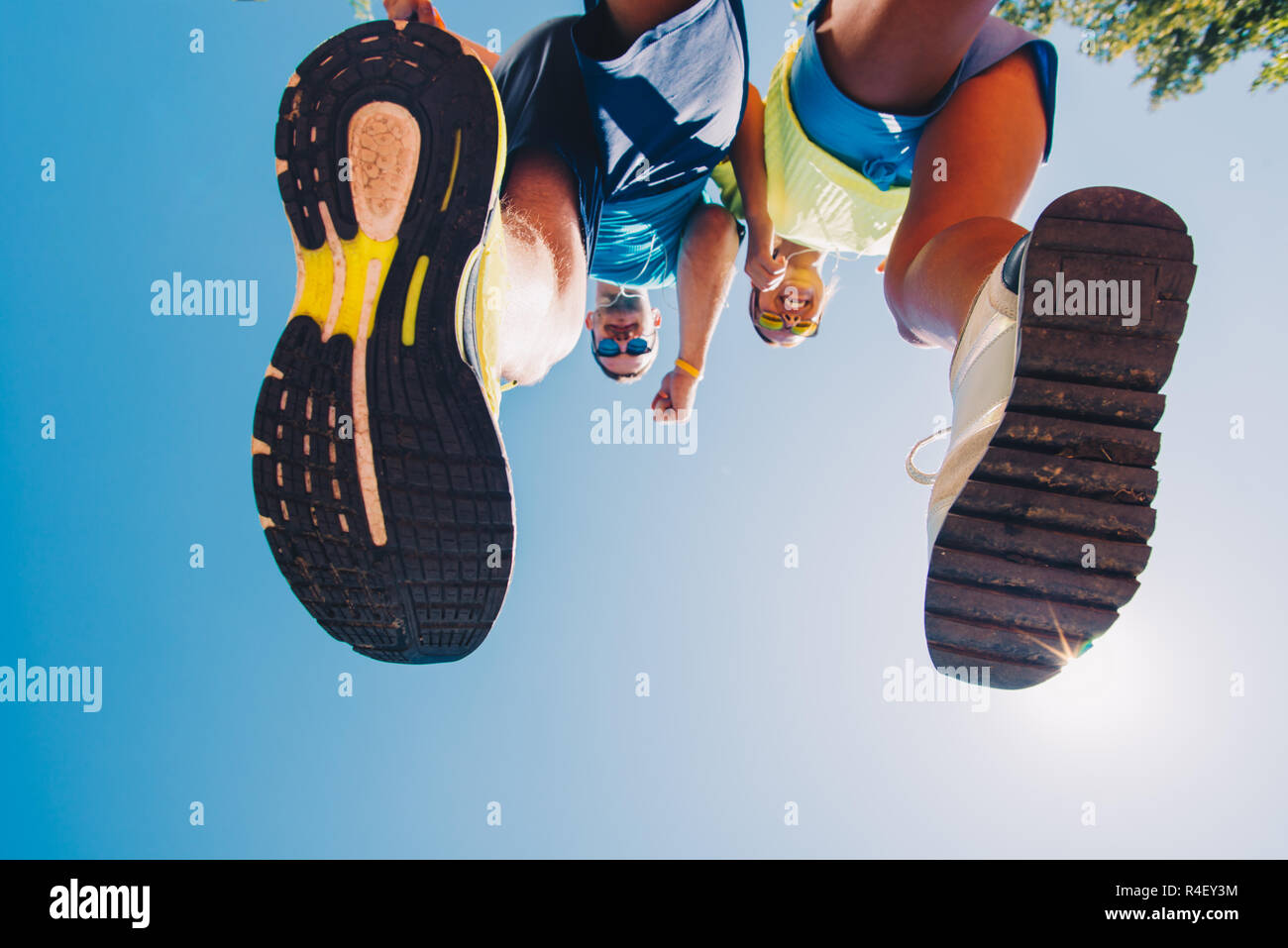 Bottom view cropped image of two people in sneakers while running Stock Photo