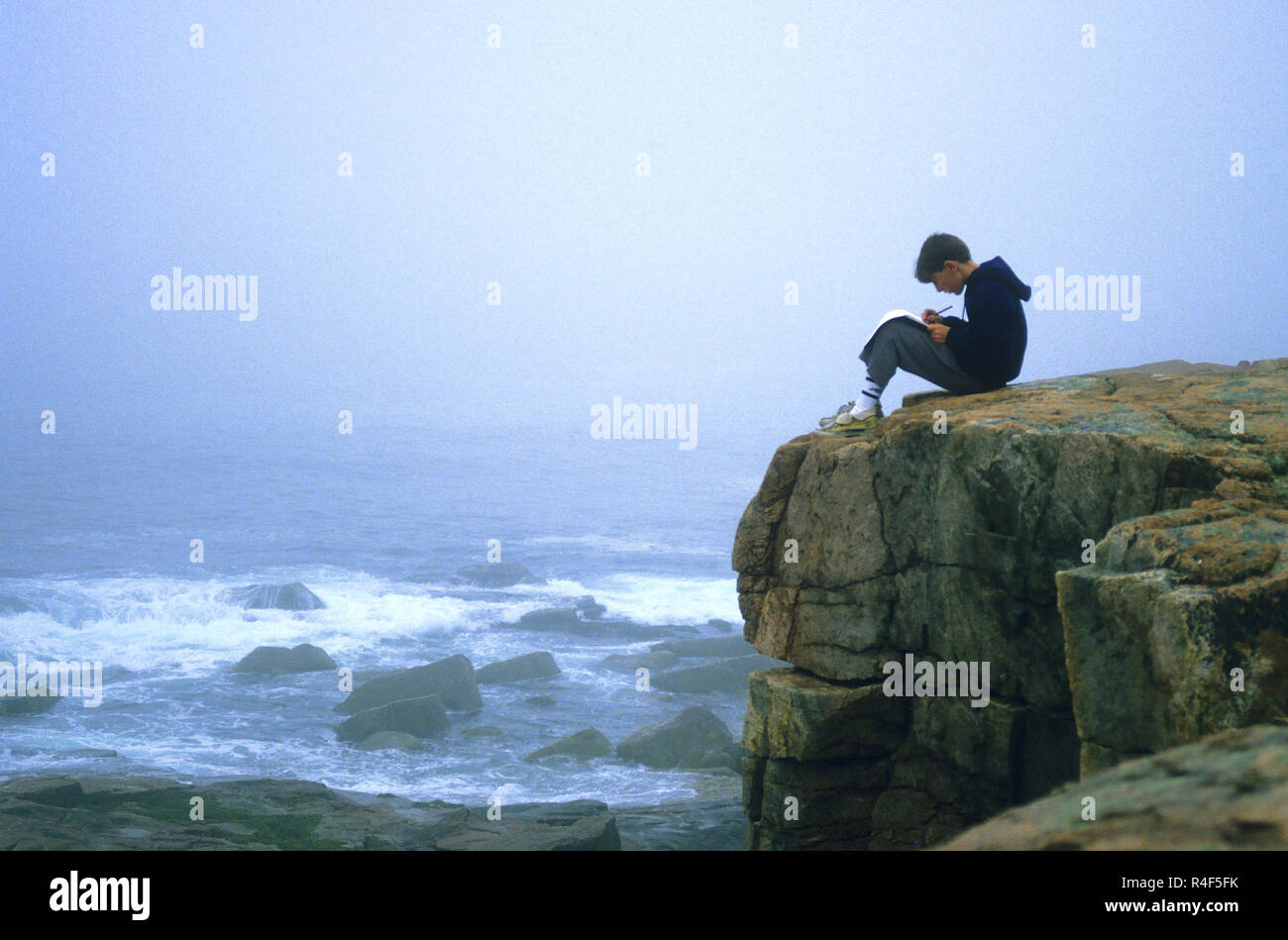 A young boy writing on the rocks of Acadia National Park, Maine, USA - Stock Image