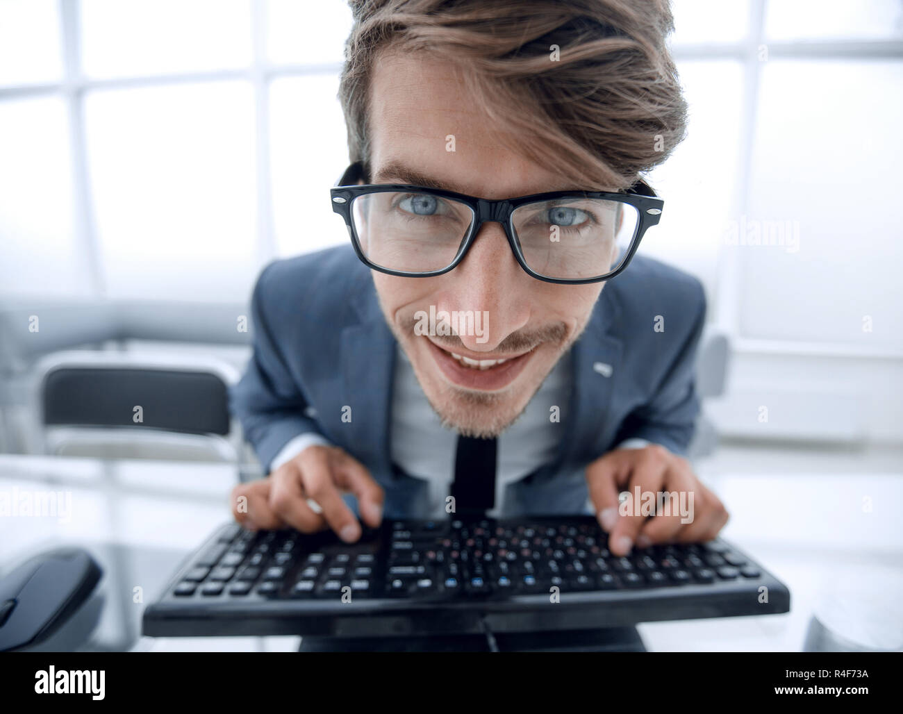 Crazy looking man typing on the keyboard - Stock Image