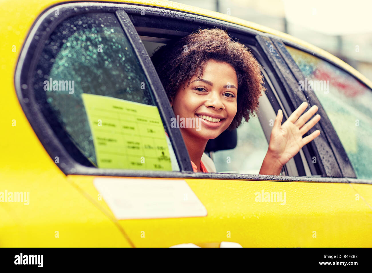 happy african american woman driving in taxi - Stock Image
