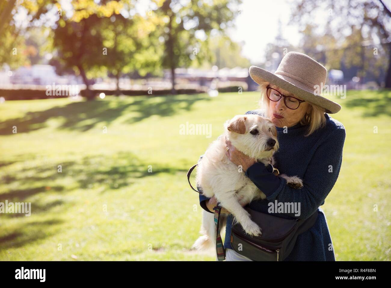 A Mature Women Kissing a Dog In Park - Stock Image