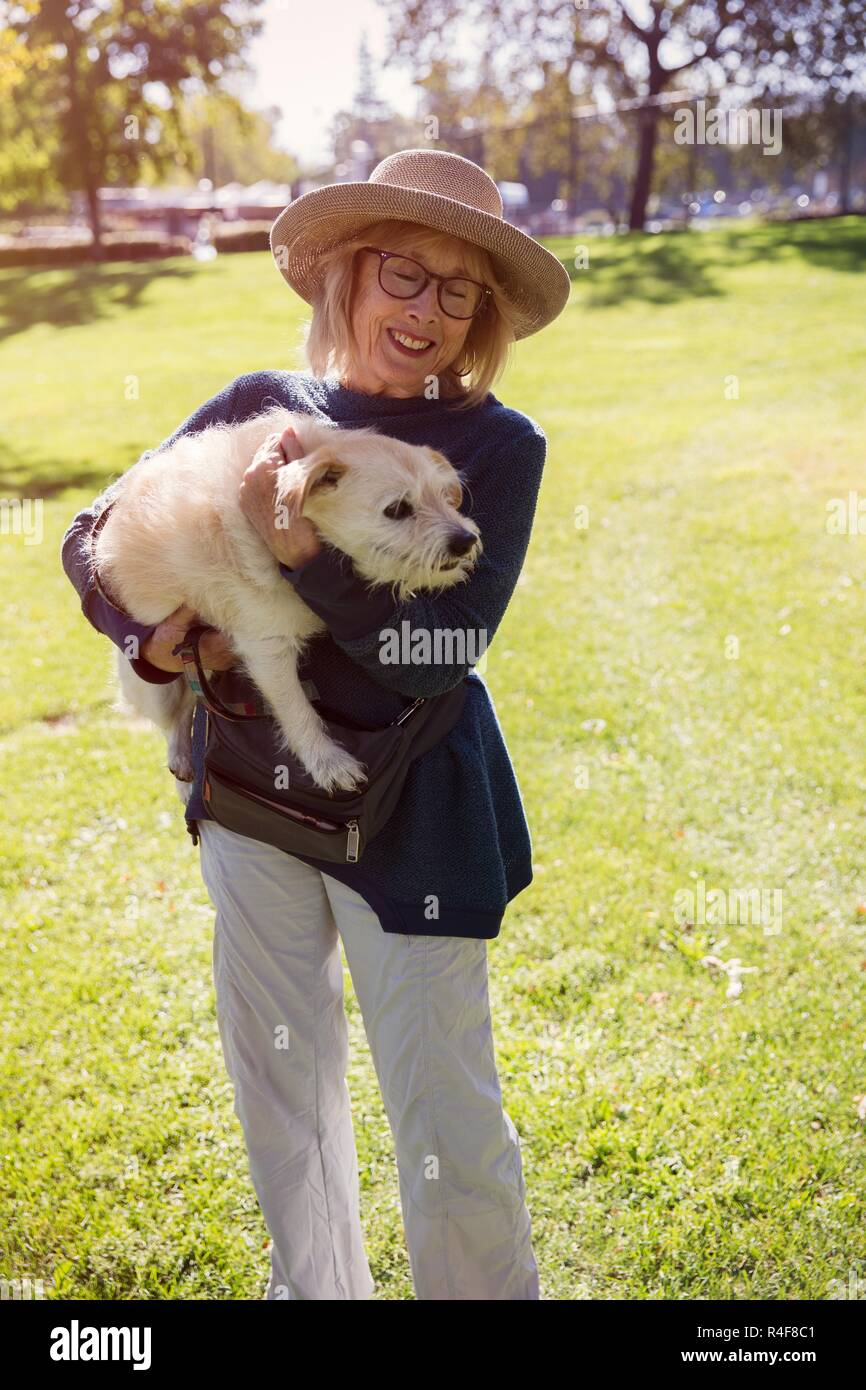 A mature women holding a dog in park. - Stock Image