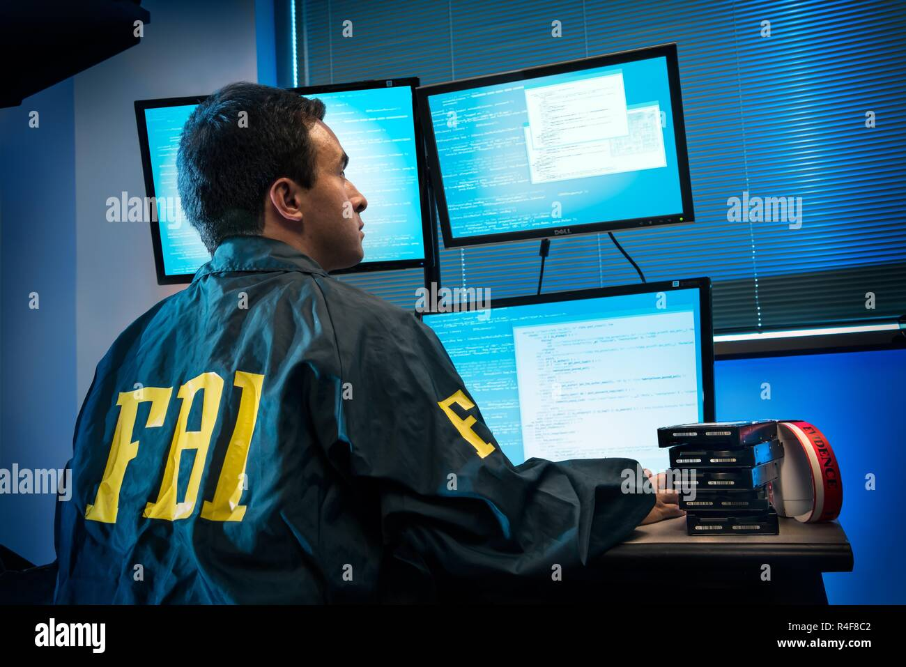 Federal Bureau of Investigation - FBI -agents work at computer in the bureau's cyber crimes division. The FBI Cyber Division is a Federal Bureau of Investigation division which heads the national effort to investigate and prosecute internet crimes, including 'cyber based terrorism, espionage, computer intrusions, and major cyber fraud.' This division of the FBI uses the information it gathers during investigation to inform the public of current trends in cyber crime.Federal Bureau of Investigation It focuses around three main priorities: computer intrusion, identity theft, and cyber fraud. - Stock Image