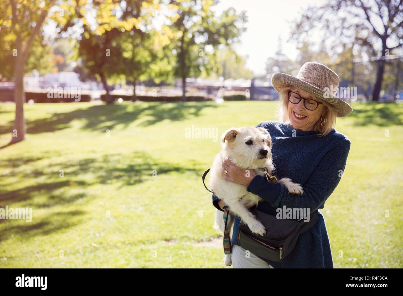 Old Woman Holding a Dog - Stock Image