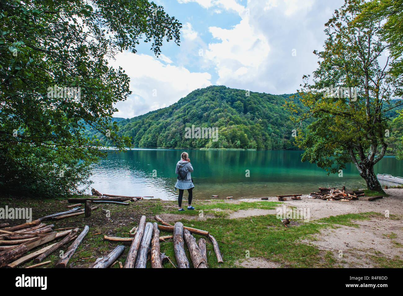 The girl on the shore of one of the most amazing lakes Plitvice in Croatia speaks on the smartphone. Pathological attachment to the means of communica - Stock Image